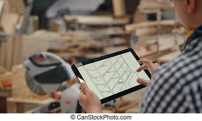 Close-up of woodworker using tablet at work looking at furniture design