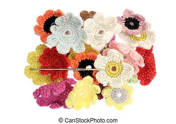 close up of woolen flowers against white blackguard.