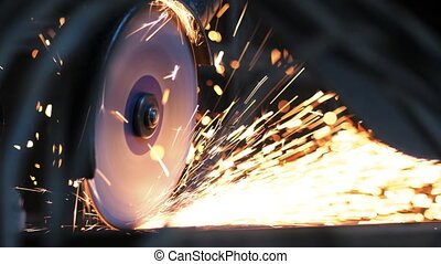 Close-up of worker at construction plant saws metal using...