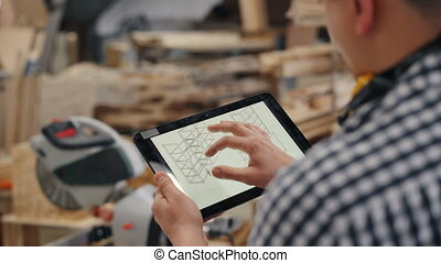 Close-up of worker touching tablet screen with design of handmade furniture