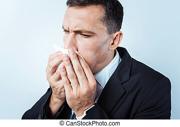 Close up of worried man sneezing