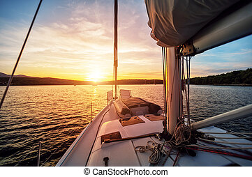 Close-up of yacht sailing against beautiful sunset. Sport...
