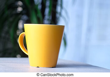 Close up of yellow color coffee cup on table