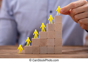 Yellow Human Figures Leading On Top Of Wooden Blocks
