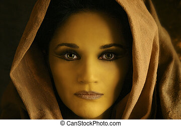 close up of yellow woman's face with brown robe wrapped...