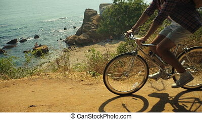 Close up of young active tourist riding bicycle on the stony beach.