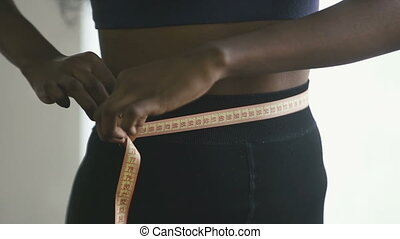 Close-up of young adult black woman in sports clothing at home, african american girl measuring waist with yellow tape close up in slowmotion