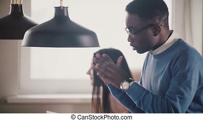 Close-up of young African American businessman talking, showing gestures, playing with little football in modern office.