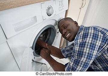 Technician Repairing Washing Machine