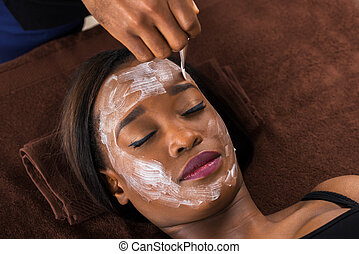 African Woman Applying Facial Mask In Spa