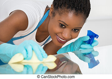 Woman Using Spray To Wipe Glass Desk - Close-up Of Young...