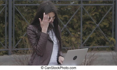 Close-up of young attractive businesswoman using laptop on a break outdoor