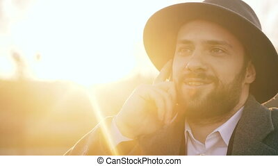 Close up of young attractive hipster man talking smartphone outdoors on sunset evening