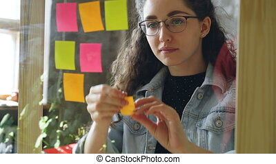 Close-up of young attractive woman wearing glasses sticking colored memos on glass board in modern office. She is looking at bright notes and smiling.