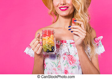 Close up of young beautiful woman with fruit jar on pink background
