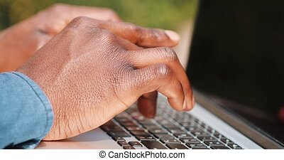Close up of young black man hands. He is wearing a shirt and typing at his laptop keyboard. Concept of a freelance job. Locked down real time close up shot