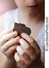Close Up of Young Boy Eating A chocolate candy