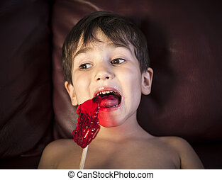 Boy Eating A Lollipop - Close Up of Young Boy Eating A...