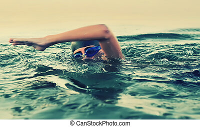Close up of young boy swimming in sea