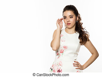 Close-up of young brunette woman in white dress on white background. professional hairstyle. Free space for your text