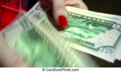 close up of young business woman counts pack of money in hands