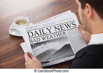 Businessman Reading Weather News On Newspaper