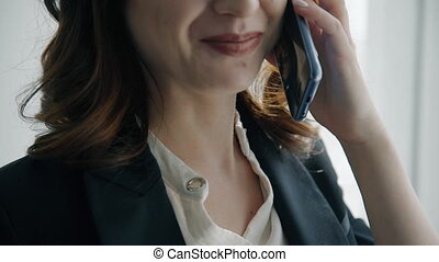 Close up of young businesswoman talking on phone.