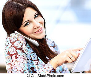 Close up of young businesswoman using digital tablet and mobile phone over building background