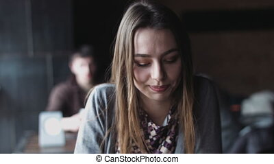 Close-up of young caucasian female sitting at the european cafe and talking to a man.