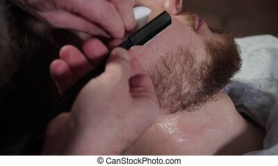 Close-up of young client shaving beard with straight razor at barber shop