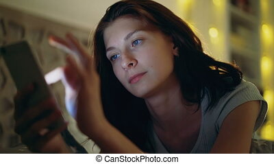 Close-up of young concentrated woman using smartphone lying in bed at home at night