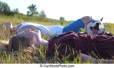 Close up of young couple in love lying on green grass at field with their siberian husky dog and relaxing at sunny day. Beautiful girl with blonde hair stroking her pet at nature. Low angle view