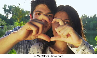 Close-up of young couple making a heart shape at sunset