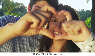 Close-up of young couple making a heart shape at sunset and kissing