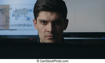 Close up of Young engineer man is working on a laptop computer at dark room