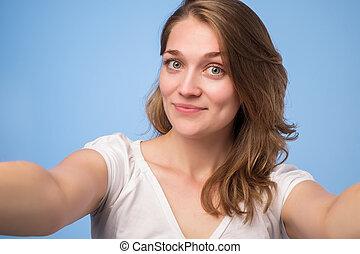 Close-up of young european beautiful woman taking selfie.