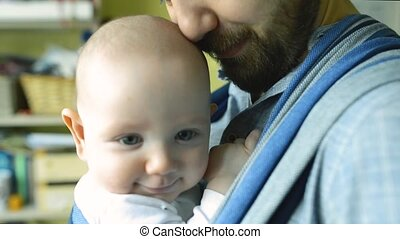 Close up of young father with his son in sling - Close up of...