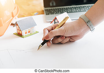 Close up of Young Female Architect Freehand Drawing, Civil engineer sketching a blueprint of construction project with small house model and safety helmet in office, Construction Concept.
