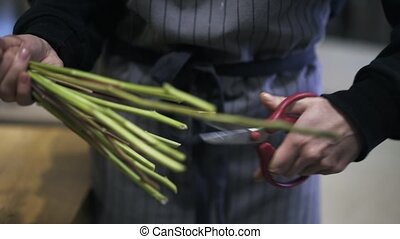Close up of young florist trimming flower stems in a shop