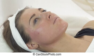 Close up of young girl face on cosmetic procedures in beauty saloon. Moistening