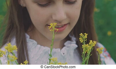 Close up of young girl holds the bouquet of rape flowers and smiling at camera
