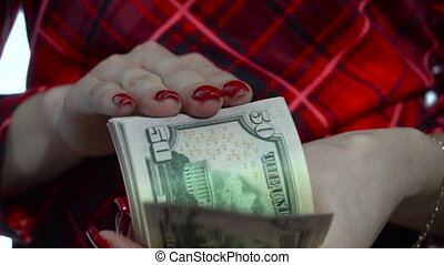 close up of young girl in red dress counts a pack of money in hands in slow motion