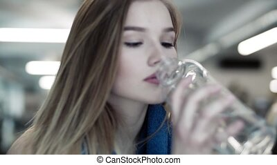 Close-up of young girl or woman in a gym, drinking water...