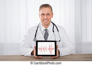 Male Doctor Showing Heartbeat On Digital Tablet
