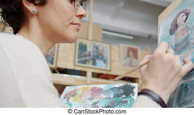 Close-up of young lady painter creating beautiful picture ...