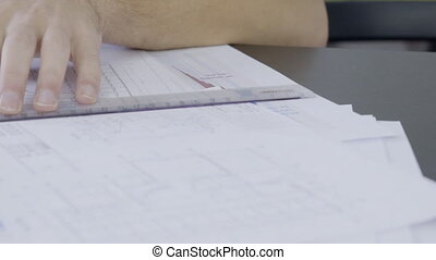 Close up of young male architect working in his office on the blueprint.