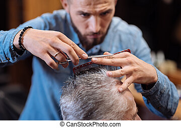 Close up of young male hairdresser cutting hair