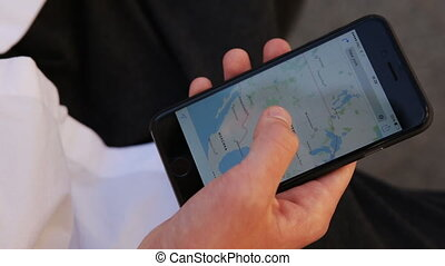 Close-up of young male hands scrolling maps on smartphone