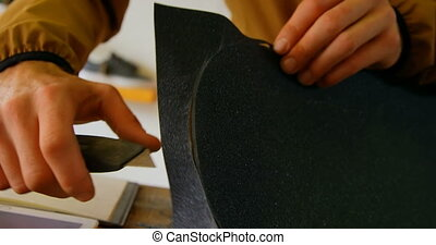 Close-up of young man cutting skateboard grip tape in a workshop. Man using cutter knife 4k
