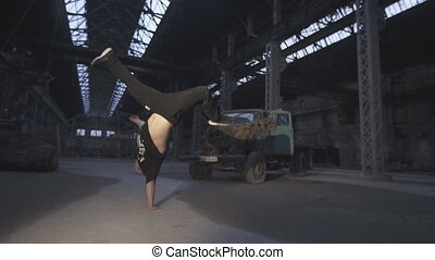 Close up of young man dancing breakdance in an abandoned building. Caucasian guy jumping on his hand indoor. Concept of healthy active lifestyle. Slow motion